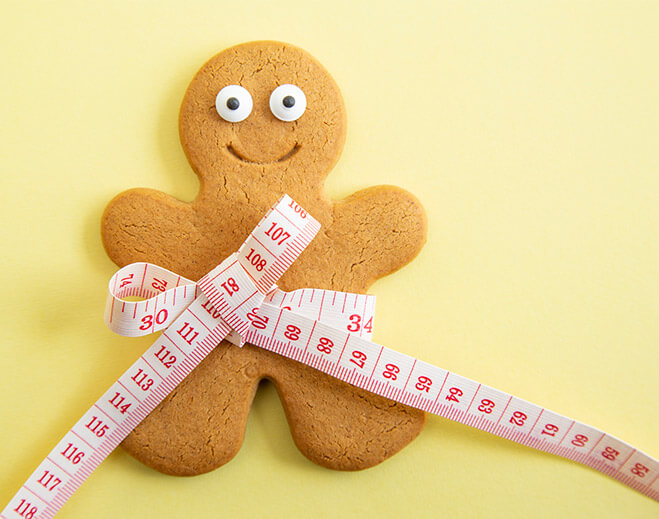 gingerbread man with measuring tape around his waist